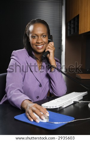 African-American young adult business woman talking on phone and working at computer in office smiling and looking at viewer. - stock photo