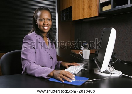 African-American young adult business woman working at computer in office smiling and looking at viewer. - stock photo