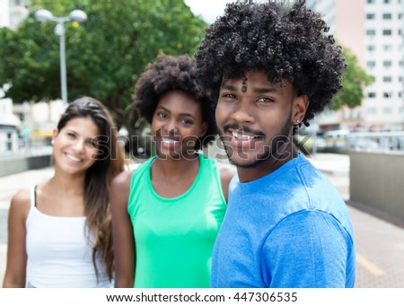 African american young adult with two beautiful girls in the city - stock photo