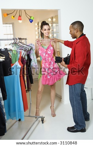 African American young male adult photographer holding dress up to young adult Caucasian female model.