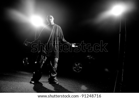 African American young man wearing baggy clothing posing under dramatic lighting with lens flare. - stock photo