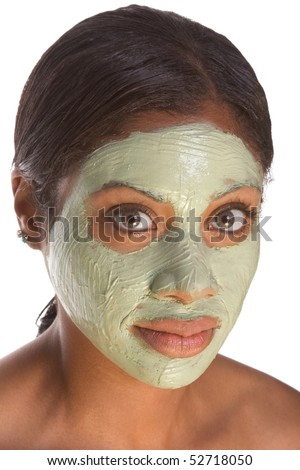 African-American young woman relaxed with facial mask, undergoing skincare procedure - stock photo