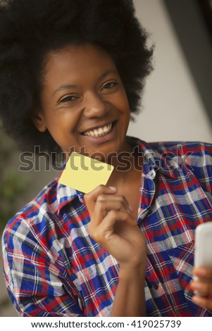 African american young woman shopping online with mobile phone and credit card - stock photo