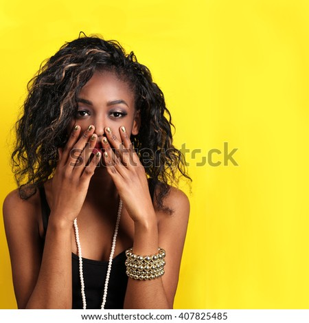 African American young woman with curly hair - easy to extend background for copy space over yellow. glamor portrait of beautiful sexy black woman model with bright makeup with perfect clean skin. - stock photo