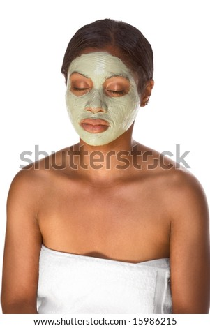African-American young woman wrapped in towel sitting relaxed with closed eyes and facial mask, undergoing skincare procedure