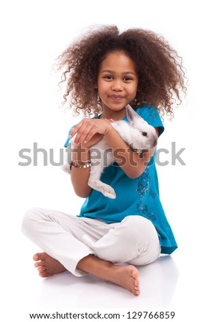 African Asian girl holding a rabbit, isolated on white background - stock photo