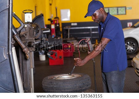 african auto mechanic pumping car tyre - stock photo