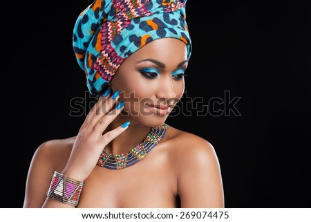 African beauty. Beautiful African woman wearing a headscarf and necklace and looking away while standing against black background - stock photo