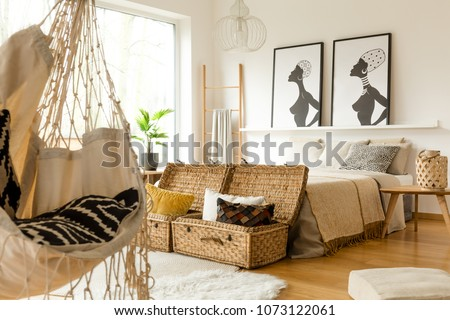 African Bedroom Interior With A Swing, Boxes With Pillows, Double Bed And  Posters