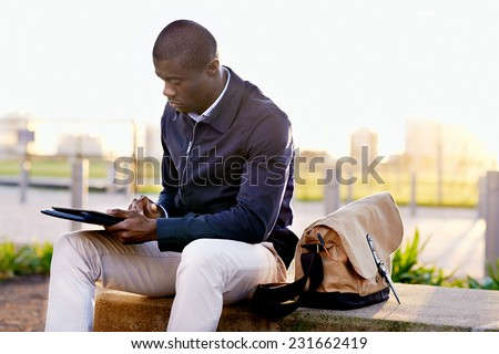 African black business man hipster using tablet computer in park on break from work - stock photo