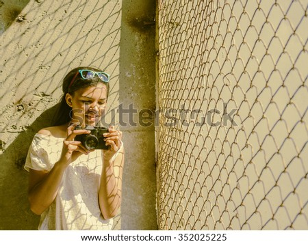 African black young adult woman hold old retro vintage photo camera on concrete texture wall background Shadows on dark skin from Sun light Cute girl make photo near metal rusty metal fence - stock photo