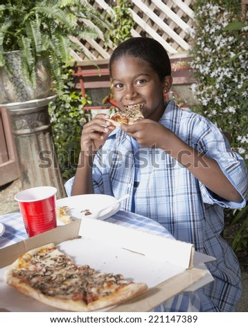 African boy eating pizza - stock photo