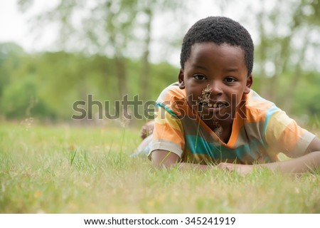 African boy is relacing in the grass - stock photo