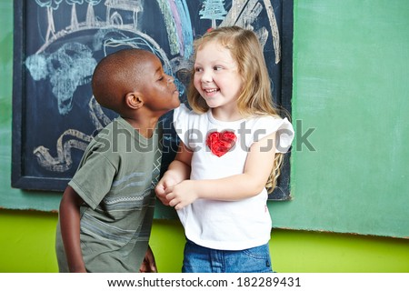 African boy kissing happy girl on the cheek in a kindergarten - stock photo