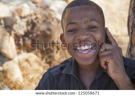 african boy on cell phone outside - stock photo