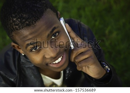 african boy on cell phone outside sitting on  grass - stock photo