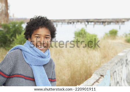 African boy wearing scarf outdoors - stock photo