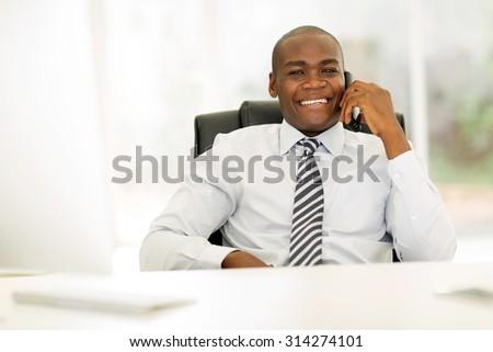 african business man talking on landline phone in modern office - stock photo