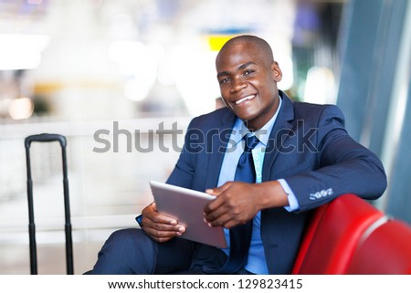 african business traveller using tablet computer at airport - stock photo