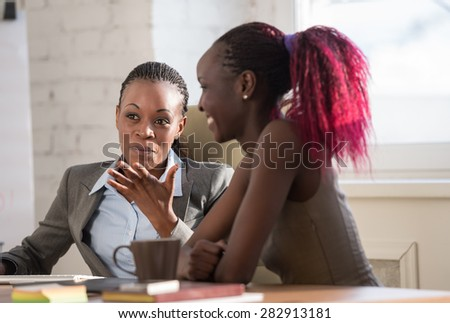 African business woman explaining something to her young colleague - stock photo