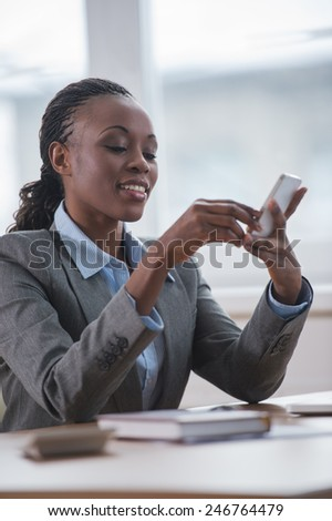 African Business woman texting with smartphone at office - stock photo