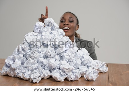 African business woman with crumpled pile of papers at workplace at office - stock photo