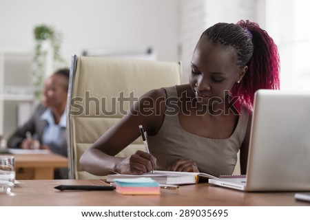 African business woman working in office environment using laptop - stock photo