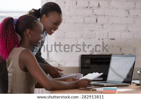 African business woman working with laptop and her colleague - stock photo