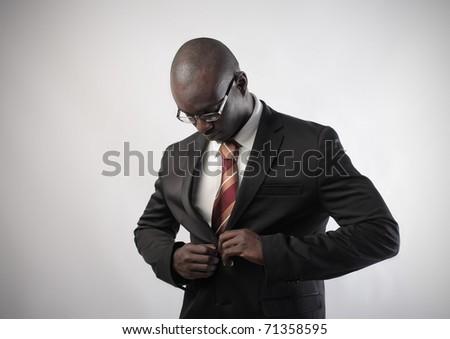 African businessman adjusting his jacket - stock photo