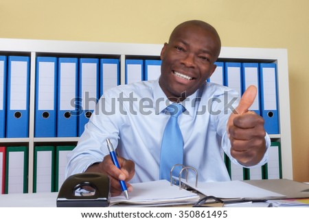 African businessman at office showing thumb - stock photo