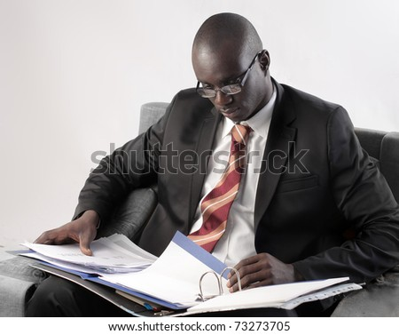African businessman folding a copybook - stock photo
