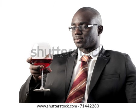 African businessman holding a glass of wine - stock photo
