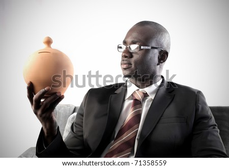 African businessman holding a money box - stock photo