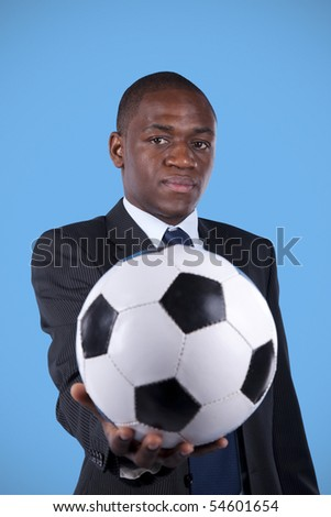 African businessman holding a soccer ball - stock photo