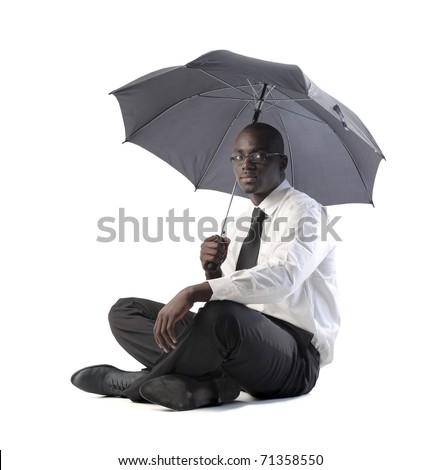 African businessman holding an umbrella - stock photo