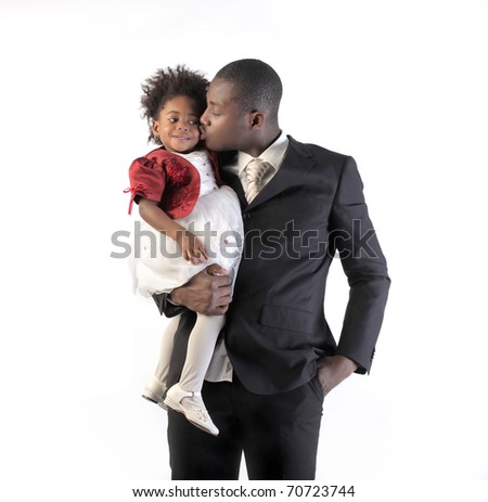 African businessman kissing her little daughter - stock photo
