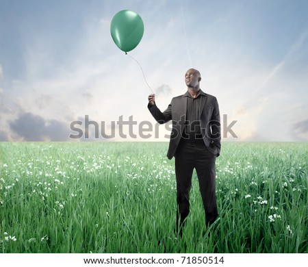 African businessman on a green meadow holding a balloon - stock photo