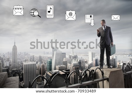 African businessman on a skyscraper and using a mobile phone with icons on the background - stock photo