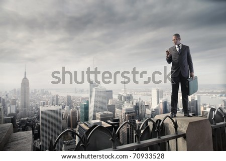 African businessman on a skyscraper using a mobile phone - stock photo