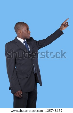 african businessman pointing to the copyspace - stock photo