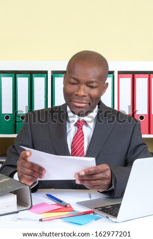 African businessman reading a message  - stock photo