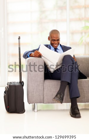 african businessman reading newspaper in airport vip lounge - stock photo