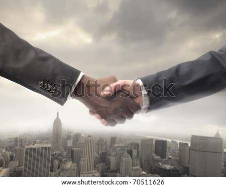 African businessman's hand shaking white businessman's hand with cityscape on the background - stock photo