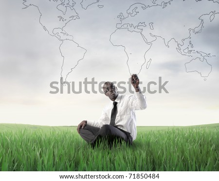 African businessman sitting on a green meadow and drawing a world map - stock photo
