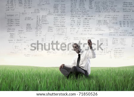 African businessman sitting on a green meadow and writing statistics - stock photo