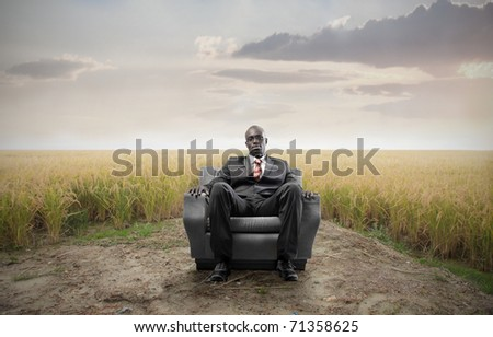 African businessman sitting on an armchair on a field - stock photo