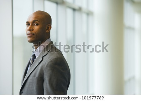African businessman standing next to window - stock photo