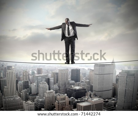 African businessman standing on a cable over a city - stock photo