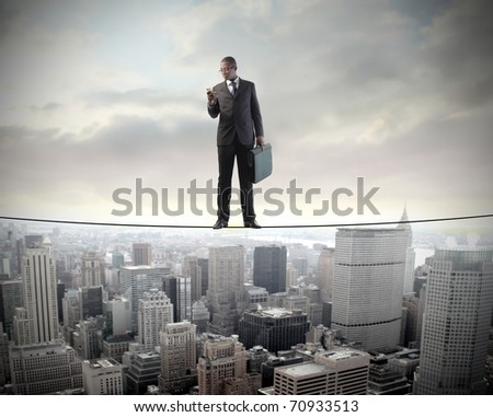 African businessman standing on a cable over a cityscape and using a mobile phone - stock photo