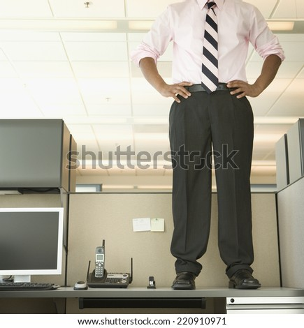 African businessman standing on desk - stock photo
